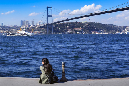 koprusu: Istanbul, Turkey - March 10, 2013: View of the European side of Istanbul from the Bosphorus. On the shore watching a woman views. The Bosphorus Bridge (Turkish: Bogazici Koprusu), also called the First Bosphorus Bridge, is one of two suspension bridges sp Editorial