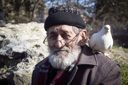 bespectacled man: Istanbul, Turkey - January 01, 2015: White Bearded Grandfather and Pigeons friendly. Istanbul Topkapi bird markets, bird seller grandfather, was seen with pigeon on shoulder.