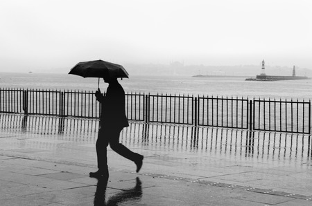 kadikoy: Rainy Istanbul coast, people and ships. Istanbul European Side appears in the background Stock Photo