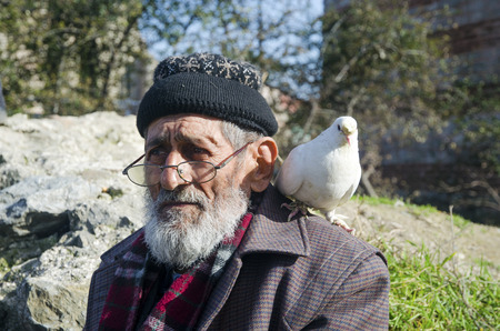 Istanbul, Turkije - 1 januari 2015: White Bearded Grandfather en duiven vriendelijk. Istanbul Topkapi-vogelmarkten, grootvader van de vogelverkoper, werd met duif op schouder gezien. Redactioneel