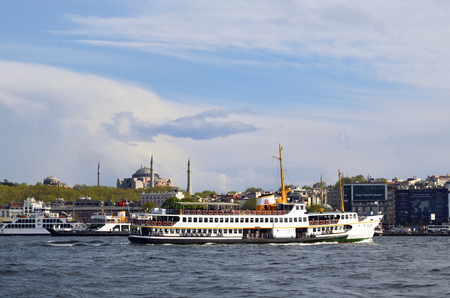 appears: Istanbul, Turkey - April 18, 2014: Istanbul Ferry and Hagia Sophia Museum. Passenger ferry in Istanbul and it appears in the background Hagia Sophia Museum