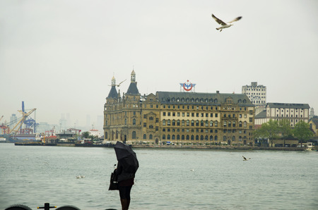 Istanbul, Turkey - April 18, 2014: Istanbul Kadikoy Steamboat pier and Haydarpasa train station building.  People walking in the rain pier. Strait of Istanbul, Kadikoy Pier, ferries are the most popular form of public transport in Istanbul for.