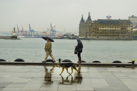haydarpasa: Istanbul, Turkey - April 18, 2014: Istanbul Kadikoy Steamboat pier and Haydarpasa train station building.  People walking in the rain pier. Strait of Istanbul, Kadikoy Pier, ferries are the most popular form of public transport in Istanbul for.