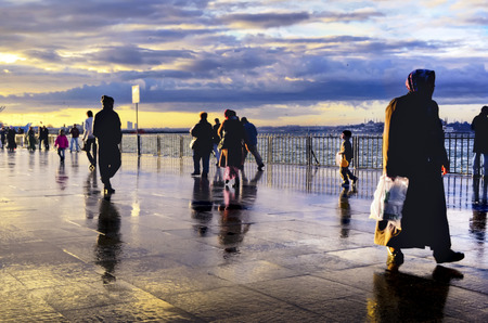appears: Istanbul, Turkey - January 19, 2013: Rainy Istanbul coast people. Istanbul European Side appears in the background