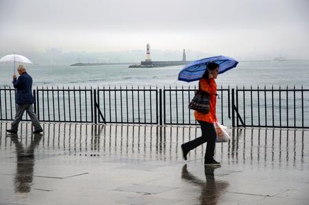 Istanbul, Turkey - April 18, 2014: Istanbul Kadikoy Steamboat pier. People walking in the rain pier. Strait of Istanbul, Kadikoy Pier, ferries are the most popular form of public transport in Istanbul for.