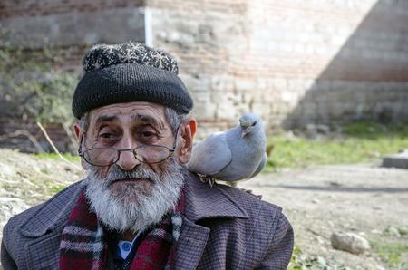 Istanbul, Turkije - 25 januari 2015: White Bearded Grandfather en duiven vriendelijk. Istanbul Topkapi-vogelmarkten, grootvader van de vogelverkoper, werd met duif op schouder gezien.