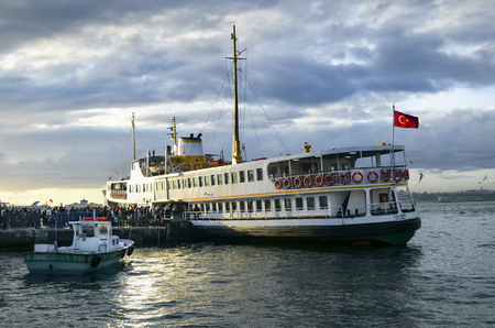 Istanbul, Turkey - January 19, 2013:  Ferry passengers from the pier. Boats have traversed the waters of the Bosphorus for millennia and until the opening of the first Bosphorus bridge in 1973, were the only mode of transport between the European and Asia