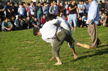 wrestlers: Istanbul, Turkey - October 2, 2016: The Central Asian Turkmen meadow wrestling held in Istanbul. Zeytinburnu district of Istanbul in the meadow, Turkmen, Uzbek, Afghan, Tatar, Kyrgyz and other Central Asian Turkmen done wrestling. Wrestling following tür Editorial