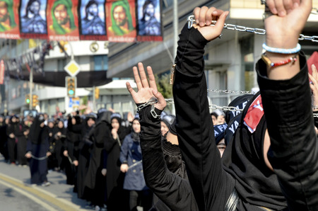 marking up: Istanbul, Turkey - October 11, 2016: Shiite Muslim women hold up their chained hands as they mourn during an Ashura procession. Turkish Shia Muslims mourning for Imam Hussain. Caferis take part in a mourning procession marking the day of Ashura in Istanbu Editorial