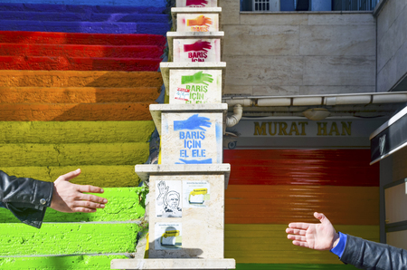colorized: Istanbul, Turkey - February 02, 2014: The hand writes Alliance for Peace on the Image. Two man poses with hand. Stairs in the Cihangir and Findikli neighborhoods, which attracts attention after being painted in the colors of a local man on August 27, 20 Editorial