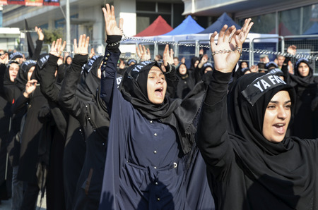 middle eastern clothing: Istanbul, Turkey - October 11, 2016: Shia Muslim women shout Islamic slogans as they mourn during an Ashura procession. Turkish Shia Muslims mourning for Imam Hussain. Caferis take part in a mourning procession marking the day of Ashura in Istanbuls Kucu Editorial