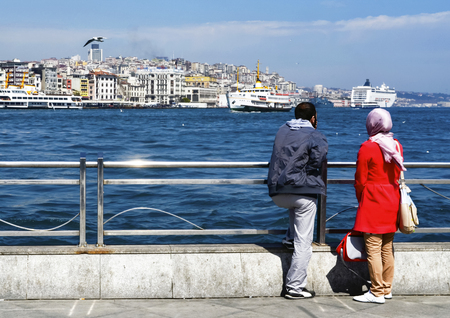 Istanbul, Turkey - March 29, 2013: On the pier Eminonu Istanbul People watching landscape. Boats have traversed the waters of the Bosphorus for millennia and until the opening of the first Bosphorus bridge in 1973 were the only mode of transport between t