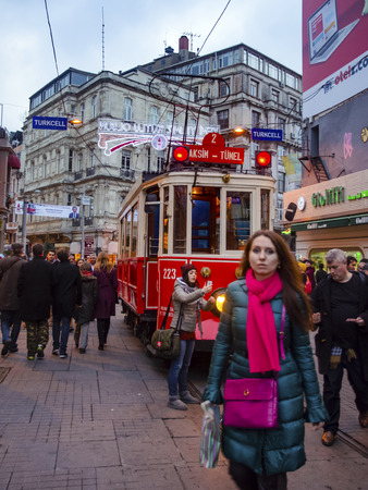 Istanbul, Turkey - December 29, 2013: Historic tram on Istiklal Avenue. People from different countries create cultural mosaics on this street. Istiklal Avenue in the Beyoglu district of Istanbul. A historic tram in front of the Beyoglu station of Tunel ( Editorial