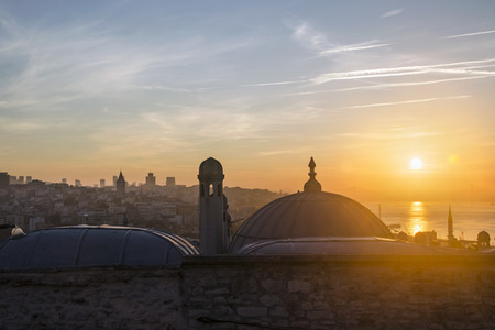 Suleymaniye Mosque from the garden Sunrise view of Istanbul. The sun rises through the throat of Istanbul.
