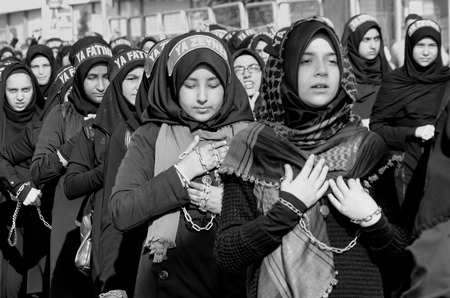 mohammed: Istanbul, Turkey - October 11, 2016: Shia Muslim women shout Islamic slogans as they mourn during an Ashura procession. Turkish Shia Muslims mourning for Imam Hussain. Caferis take part in a mourning procession marking the day of Ashura in Istanbuls Kucu Editorial