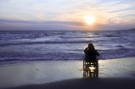 Sunset on the beach handicapped woman in wheelchair. Stok Fotoğraf