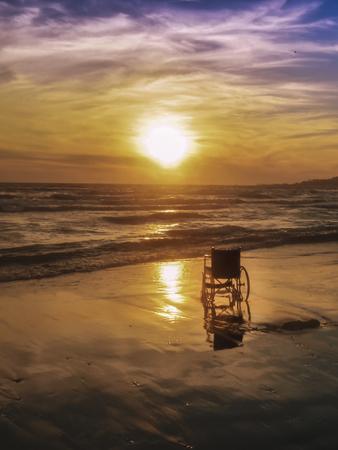 Sonnenuntergang am Strand Behinderte Rollstuhl. Hintergrund Standard-Bild - 70810045