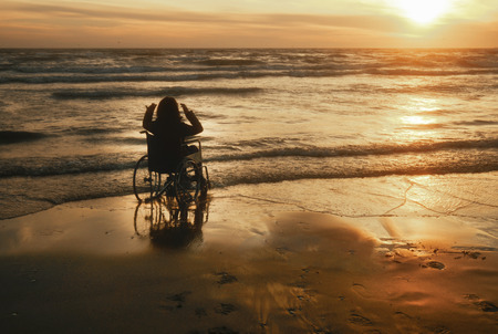 Sonnenuntergang am Strand behinderte Frau im Rollstuhl. Standard-Bild - 70810046