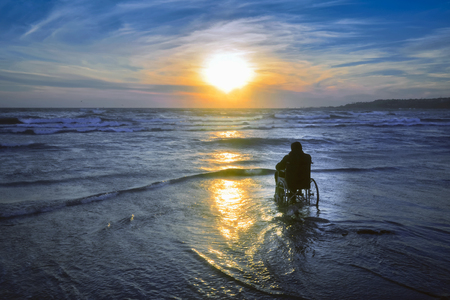 unable: Sunset on the beach handicapped man in wheelchair. Stock Photo
