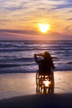 Sonnenuntergang, macht Sightseeing am Strand eine Frau auf einem Rollstuhl Standard-Bild - 70810051