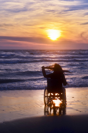 Sunset, makes sightseeing on the beach a woman on a wheelchair Stok Fotoğraf