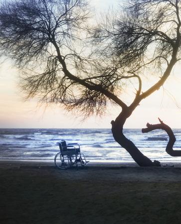 Sonnenuntergang am Strand Behinderte Rollstuhl. Hintergrund Standard-Bild - 70810052
