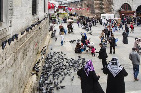 Istanbul, Türkei - 29. März 2013: Neue Moschee (Yeni Cami) Menschen und Tauben rund um den Hof. Auf der rechten Seite befindet sich das historische Gebäude mit dem Eingang zum Gewürzmarkt - Eminönü (Ägyptischer Basar). Es befindet sich am Goldenen Horn, am südlichen Standard-Bild - 67936274