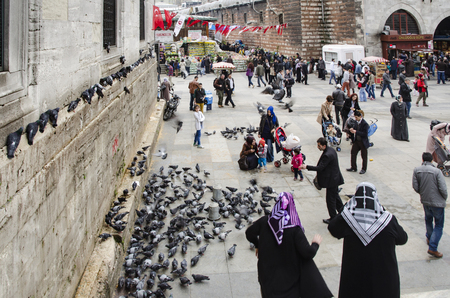 Istanbul, Turkey - March 29, 2013: New Mosque (Yeni Cami) People and pigeons around the courtyard. On the right is the historic building with the entrance to the Spice market - Eminonu (Egyptian Bazaar). It is situated on the Golden Horn, at the southern