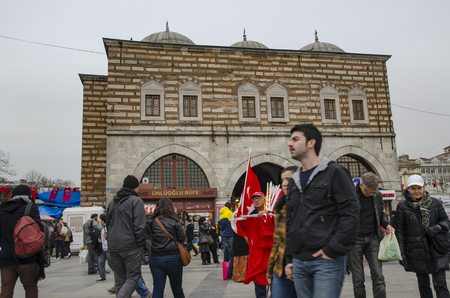 Istanbul, Turkey - March 29, 2013: The historic building with the entrance to the Spice market - Eminonu (Egyptian Bazaar) meydan. Theres a flag vendor in the middle.