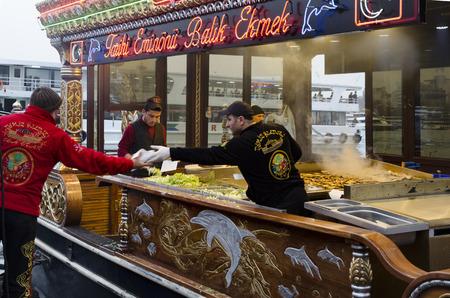 Istanbul, Türkei - 29. März 2013: Essen vom Grill Fisch-Sandwich in Eminönü. Das erste, was in den Sinn kommt, wenn man von Istanbul zu denken ist Eminönü-Karaköy und die Orte, gegrillten Fisch-Sandwiches dort am Ufer des Goldenen Horns zu verkaufen. Männer tragen reich Standard-Bild - 67936192