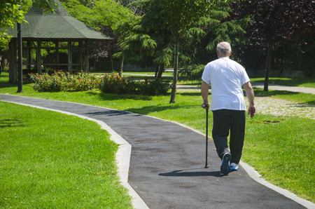 Istanbul, Turkey - June 4, 2016: An old man walking in a park on a sunny day with cane