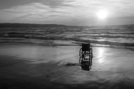 Sonnenuntergang am Strand Behinderte Rollstuhl. Hintergrund Standard-Bild - 71015248