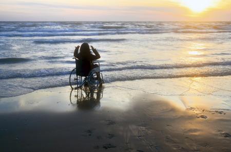 Sonnenuntergang am Strand behinderte Frau im Rollstuhl Standard-Bild - 71015251