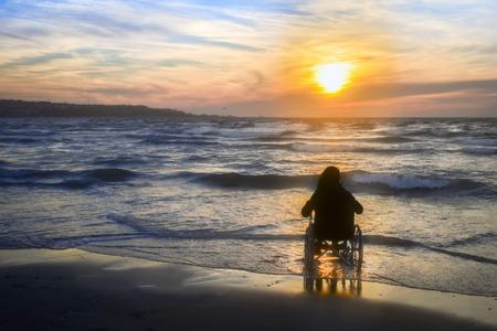 Sonnenuntergang am Strand behinderte Frau im Rollstuhl. Standard-Bild - 71015252
