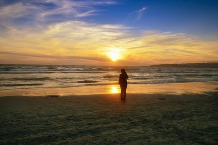 Sonnenuntergang über den Meer-, Strand-, See- und Sonnenorangenfarben. Silhouetten von Menschen erscheinen. Standard-Bild - 71015255