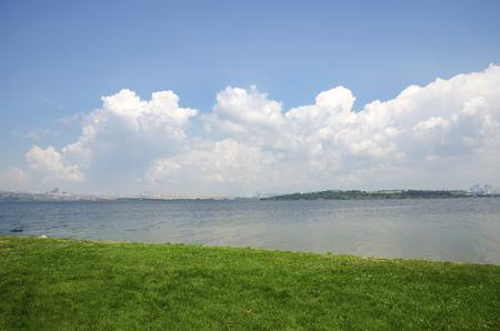 See, weiße Wolken und grüne Felder Landschaft. Der See Kucukcekmece (türkisch: Kucukcekmece Golu) ist eine Lagune zwischen den Kucukcekmece Esenyurt und Avcilar Bezirken der europäischen Teil der Provinz Istanbul, im Nordwesten der Türkei. Standard-Bild - 71015261
