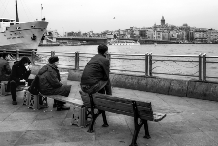 Istanbul, Turkey - February 21, 2013: Istanbul view. Eminonu pier, Galata bridge and Galata tower. People are resting on the bench.