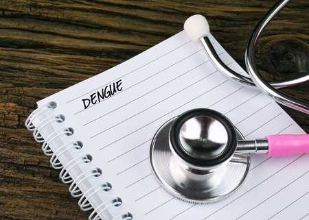 Healthcare concept. Stethoscope on notebook written with DENGUE.