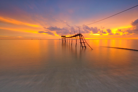 Stunning sunset at seascape with old pier background. Stock fotó