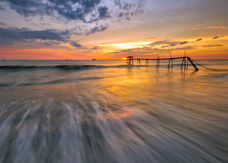 Beautiful dramatic sunset at seascape with wave motion foreground and clouds sky background.