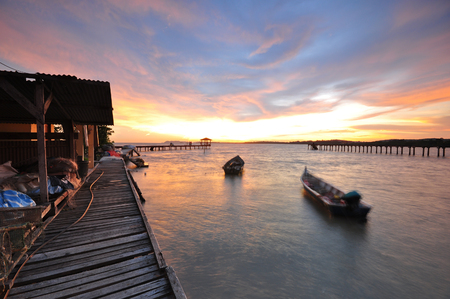 Dramatic sunset at fishermen village with boats and wooden jetty background.