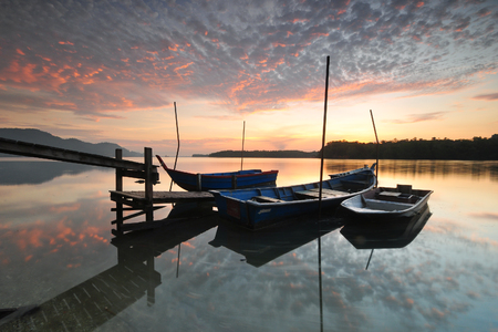 Dramatic morning scenery at over the wooden jetty and fishermen boats.