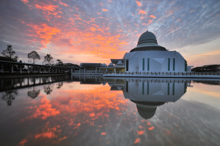 Stunning sunrise sky over the majestic mosque with reflection on the lake. Stock fotó