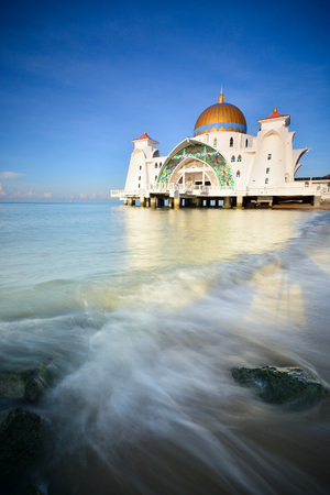 Majestic Malacca Straits Mosque with blue sky background. Wave motion at foreground. Stock fotó