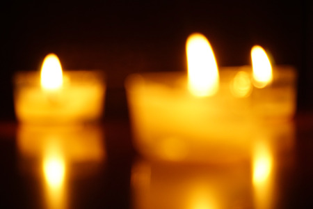 Blurred candles light flame on dark background.