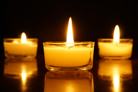 Candles light flame on dark background. Archivio Fotografico