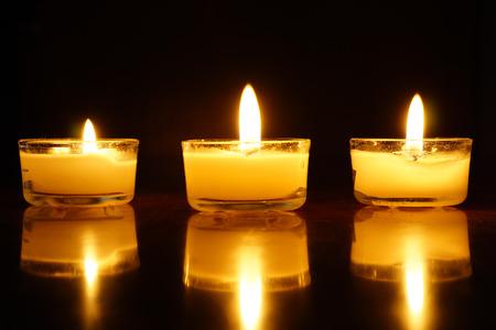 Candles light flame on dark background. Stock fotó