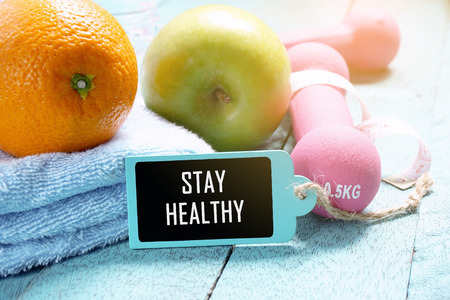 Fitness concept. Nutrition food, fitness equipment and wooden tag written with Stay Healthy on wooden background.