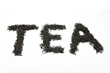 Word tea made of dry leaves isolated on white background photo