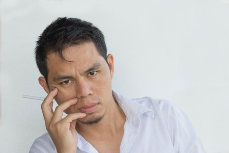 frustrating: stressful businessman smoking an cigarette on white background